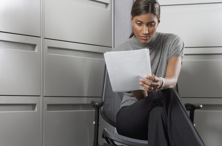 Businesswoman sitting on a chair reading