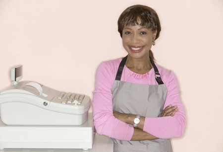 Woman standing at a cash register smiling