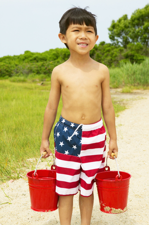 Young boy carrying two buckets at the beach Stock Photo
