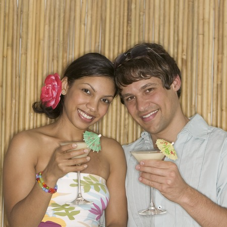 Young couple holding cocktails looking at camera