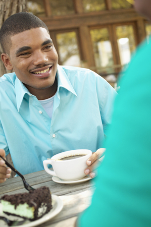 Young man sitting outdoors at a table holding a cup of coffee
