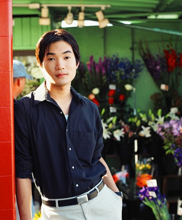 Portrait of a young man standing in a flower shop