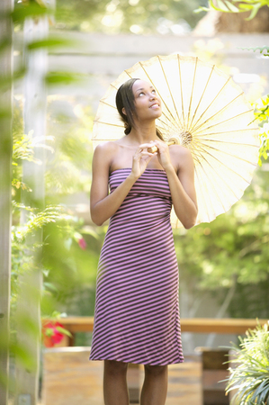 Young woman holding a parasol looking up Stock Photo