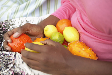 Mid section view of young woman holding fruit in her lap