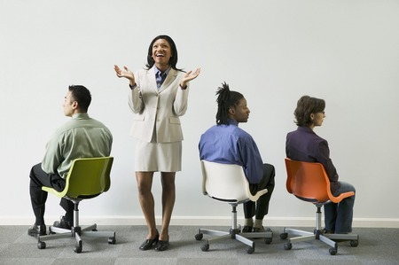 Businesswoman standing with three business executives sitting on chairs