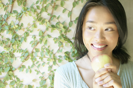Young woman holding an apple smiling