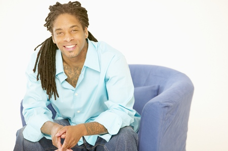Portrait of a young man sitting on a couch smiling