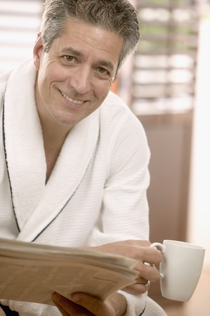 Man sitting holding a coffee cup and a newspaper