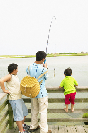 Father and his two sons standing at a pier with fishing gear