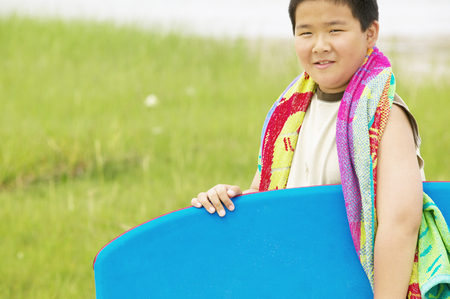 Young boy holding a boogie board smiling