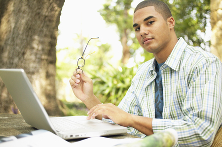 Young man sitting at a table working on a laptop