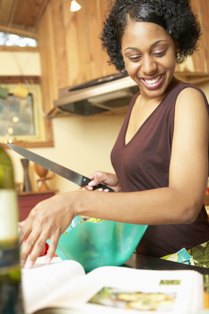Young woman holding a knife in a kitchen