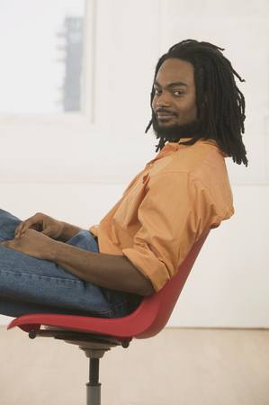 Young man sitting on a chair looking at camera