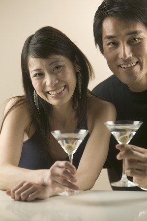 Couple holding martini glasses looking at camera
