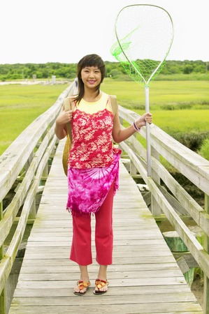 Woman standing on a pier holding a fishing net Stock Photo