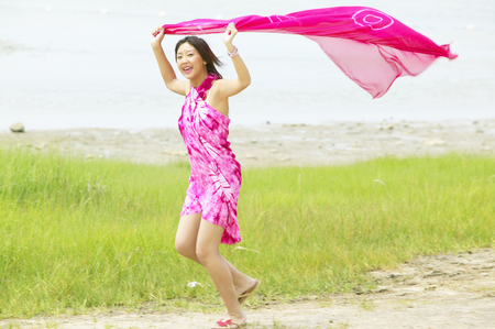 Young woman holding a sarong over her head running