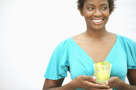 Young woman holding a glass filled with kiwi fruit