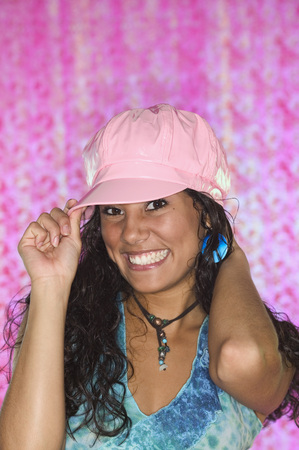 Young woman holding a cap on her had looking at camera smiling
