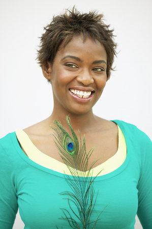 Young woman standing holding a peacock feather smiling Stock Photo