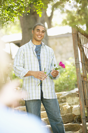 Portrait of a young man standing holding a rose Stock Photo