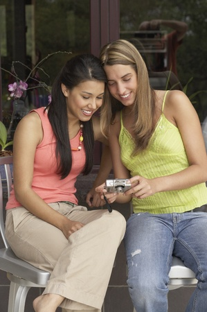 Two young women reviewing digital photos Stock Photo