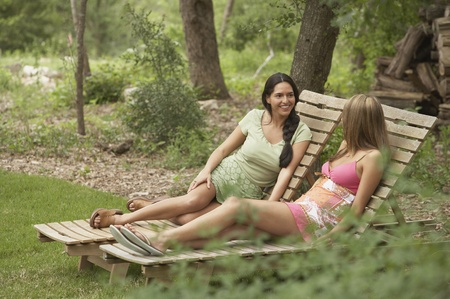 Two young women sitting on lounge chairs 版權商用圖片