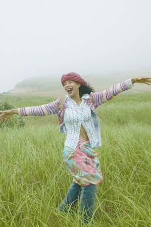Young woman in a field with her arms stretched out