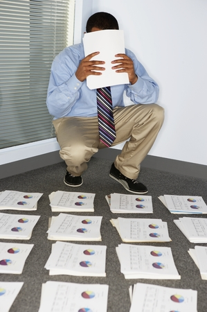 Businessman covering face with papers