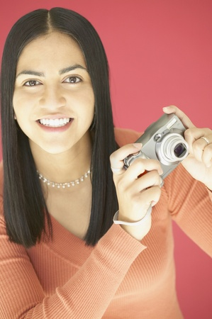 Young woman holding a camera Stock Photo