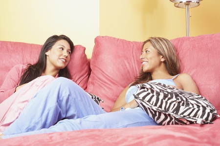 Two women sitting together on bed