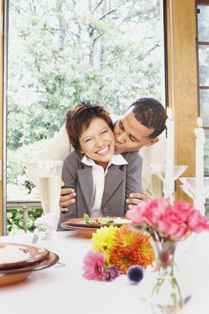 Couple kissing at the dinner table Stock Photo
