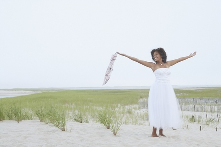 Young woman standing on the beach with her arms outstretched Stock Photo