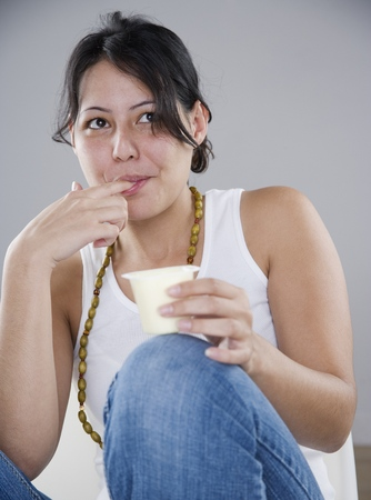 Young woman eating pudding with her fingers