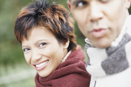 Young woman smiling for the camera beside her boyfriend Stock Photo