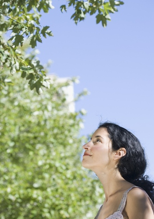 Young woman looking at tree Stock Photo