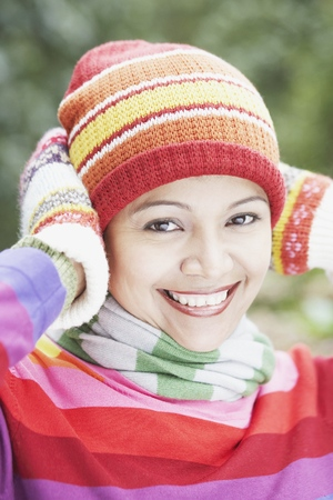 Young woman wearing a hat, scarf and gloves outdoors