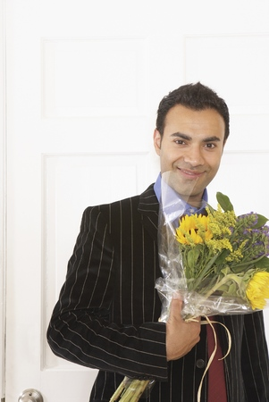 Young businessman holding a bunch of flowers
