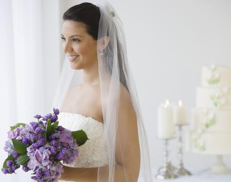 Hispanic bride holding bouquet of flowers