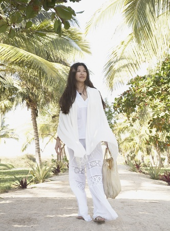 Young woman walking in tropical surroundings