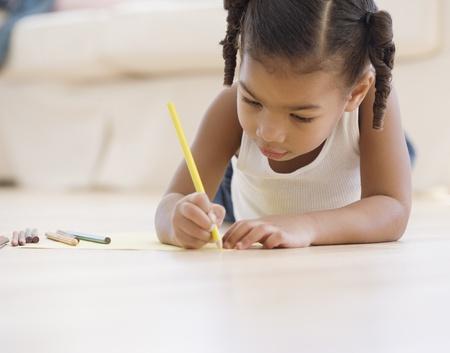 African girl coloring on floor Banco de Imagens
