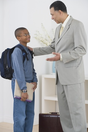 African father seeing son off to school Stock Photo