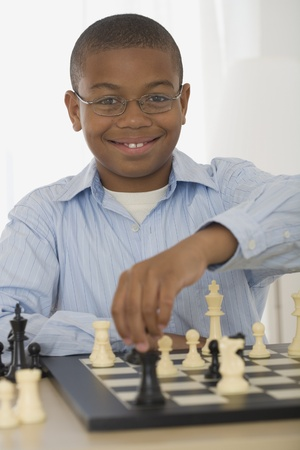 African boy playing chess 免版税图像