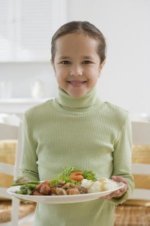Hispanic girl holding plate of food