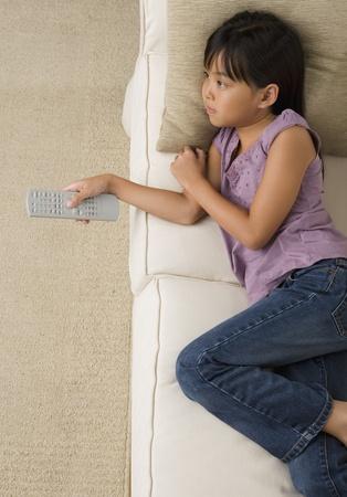 Jong Aziatisch meisje televisie kijken op de bank
