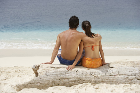 South American couple sitting at beach