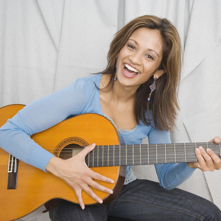 Indian woman playing acoustic guitar Imagens