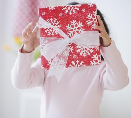 Hispanic girl holding gift in front of face Stok Fotoğraf
