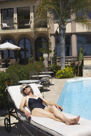 Woman at poolside laying on lounge chair Reklamní fotografie