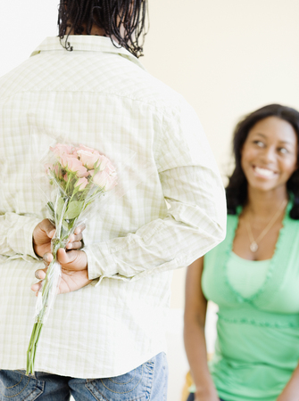 African man surprising woman with flowers Stock Photo
