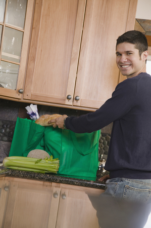 Hispanic man unloading recyclable shopping bag in kitchen Фото со стока